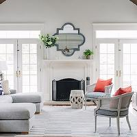 Lauren Nelson Design - living rooms - vaulted ceilings, white walls, cathedral ceilings, french doors, french doors flanking fireplace, french doors with transom windows, transom windows, hardwood floors, gray and white striped rug, striped rug, gray sectional, gray sectional sofa, contemporary gray sectional sofa, garden stool, interlocking circle garden stool, fireplace, quatrefoil mirror, vase of foliage, coral pillows, white vintage cane backed chairs, cane backed chairs, blue and white striped pillows, white media console, contemporary white media console, media console with open shelves, white parsons side table, parsons side table, silver lamps, mercury glass lamps, navy blue drapes, navy blue curtains, floor length navy blue drapes, floor length navy blue curtains, light gray sectional,