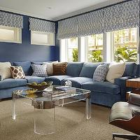 Palmer Weiss - living rooms - blue family room, family room, bold blue walls, blue family room walls, geometric roman shades, white and blue roman shades, white and blue geometric roman shades, blue geometric roman shades, blue sectional, blue sofa, blue sectional sofa, ivory pillows, white and blue pillows, white and brown ikat pillows, striped brown pillow, lucite coffee table, square coffee table, coffee table, lucite and brass coffee table, lucite coffee table with brass trim, art deco coffee table, mercury glass lamp, art deco end tables, beige rug,
