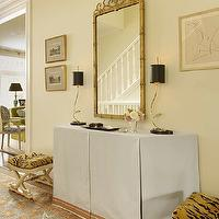 Palmer Weiss - entrances/foyers - foyer, entrance, elegant foyer, elegant entrance, skirted foyer table, skirted console table, gold and black lamps, gilded mirror, tiger stools, tiger ottomans, x stool, x ottoman, x base stool, x base ottoman, orange and blue rug, persian rug, orange and blue rug,