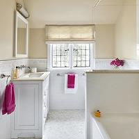 Clean Design Partners - bathrooms - Benjamin Moore - Putnam Ivory - hex floor tile, hexagonal floor tile, marble hex floor tile, hexagonal marble tiled floors, white vanity, white bathroom vanity, white sink vanity, undermount sink, white vanity mirror, white bathroom mirror, limestone counters, limestone countertops, linen roman blind, subway tile, white subway tile, thassos field tile, thassos field tiled border, thassos field tile border, hexagonal thassos field tiled border, thassos field hex tiled border, leaded glass windows, leaded windows, white subway tile with accent border, fuchsia pink towels, fuchsia pink accent towels, bath, Cloud Nine Hex Tile Floor, Thassos Field tile, Openwork Long Sconce, Jerusalem Gold Limestone Countertops,