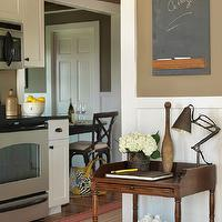 Kate Jackson Design - kitchens: white cabinets, white cabinetry, white kitchen cabinets, white kitchen cabinetry, black counters, black countertops, stainless steel appliances, stainless steel oven, stainless steel microwave, microwave oven hood, microwave hood, stainless steel microwave hood, hardwood floors, beadboard paneling, beadboard ceiling, beadboard walls, beadboard half walls, white beadboard, stained beadboard ceilings, striped red and beige rug, antique side table, stacked books, clam shell, adjustable desk lamp, vintage bowling pin, vase of hydrangeas, chalkboard, chalkboard message board, wooden ceiling, khaki wall color, khaki colored walls, dark khaki colored walls, chalkboard message board,