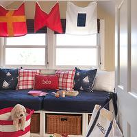 Kate Jackson Design - boy&#039;s rooms - nautical bedroom, nautical kids bedroom, nautical boys bedroom, nautical boys room, nautical theme, coastal theme, window seat, built-in window seat, window seat storage, pull-out woven baskets, window seat with basket storage, red and white plaid pillow, plaid pillow, red monogrammed pillow, navy blue boat print pillows, navy blue yacht print pillows, shag carpet, red and white basket, red and white canvas basket, striped red and white canvas basket, nautical flags, vaulted ceiling, boat flags, sailing flags, red white and blue boys bedroom, red white and blue kids bedroom, red white and blue nautical bedroom,