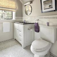 Clean Design Partners - bathrooms: traditional bathroom, white vanity, white single vanity, white sink vanity, undermount sink, black granite counters, black granite countertops, white subway tile, subway tile, white subway tiled walls, subway tiled half walls, gray walls, gray bathroom walls, gray wall color, basketweave accent tile, basketweave border, marble basketweave border, towel loop, towel holder, towel bar, roman blinds, basketweave floor tile, marble basketweave floor tile, black and white framed art, round mirror, frameless round mirror, beveled round mirror, Absolute Black Granite Countertops, Visual Comfort Lighting Openwork Long Sconce, Duralee Silk Road II fabric in seaglass, purple and gray bathroom,