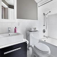 Clean Design Partners - bathrooms - white penny tile, penny tiled floors, white penny tile floors, penny tile, white subway tile, subway tiled bathroom, subway tile, subway tiled walls, toilet, bath shower combo, bath tub, bath, contemporary bathroom, chrome base sink console, chrome sink based drawer front sink console, contemporary 2-drawer sink console, trough sink, modern faucet, contemporary sink, white medicine cabinet, medicine cabinet, white glass and polished nickel sconce, gray walls, dark gray walls, gray bathroom walls, contemporary sconce, contemporary bathroom sconce, white gray and black bathroom, white black and gray bathroom, gray and black bathroom,