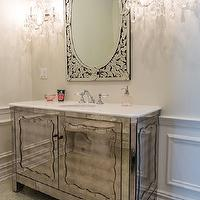 Vanessa Deleon - bathrooms - mirrored bathroom vanity, antiqued mirror vanity, antique mirrored vanity, antiqued mirrored vanity, white counters, white countertops, mirrored vanity, mirrored sink vanity, venetian mirror, venetian vanity mirror, crystal sconces, crystal bathroom sconces, wainscoting, wainscoting paneled walls, raised panel wainscoting, mosaic tiled floors, pearlescent mosaic tiled floors, ornate crystal sconces, feminine bathroom,
