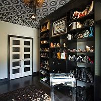 Vanessa Deleon - closets - closet, chic closet, rock and roll closet, wallpapered ceiling, black and cream wallpapered ceiling, wallpapered closet ceiling, walk-in closet, shoe storage, purse storage, handbag storage, dark hardwood floors, hardwood floors, patchwork hide rug, patchwork cowhide rug, mosaic cowhide rug, lucite chair, lucite chair with tufted seat, lucite chair with white tufted seat, black and white door, black and white closet doors, master closet, master bedroom closet, walk-in wardrobe, black hardwood floors, chain pendant, swaggered chain pendant,