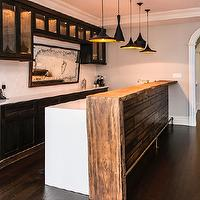 Vanessa Deleon - kitchens - wet bar, bar area, live edge countertops, wooden live edge counters, waterfall counters, waterfall countertops, dark stained wood kitchen cabinets, dark wood cabinets, dark cabinets, white waterfall edge counters, white waterfall edge countertops, white subway tile backsplash, subway tile, white subway tile, subway tiled backsplash, herringbone patterned backsplash, white subway tile herringbone backsplash, subway tiled herringbone backsplash, herringbone backsplash, wood paneled peninsula island, peninsula island, live wood edged counters, live edge countertops, dark hardwood floors, glass front cabinets, glass fronted cabinets, brass foot rail, bar foot rail, hardwood floors, gray walls, white crown molding, crown molding, baseboards, arched doorways, Beat Lights,