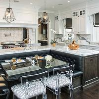 Vanessa Deleon - kitchens - l-shaped kitchen, l-shaped banquette, built-in banquette, hardwood floors, dark hardwood floors, recessed lighting, pot lights, white cabinets, white cabinetry, white kitchen cabinets, white kitchen cabinetry, white marble counters, white marble countertops, pot filler, pot filler faucet, stainless steel oven, paneled oven hood, oven hood, l-shaped kitchen island, l-shaped island, l-shaped island with banquette, black button tufted banquette, prep sink, prep sink in kitchen island, prep sink in island, black tufted banquette, lucite chairs, dining chair with caramel colored upholstery, seamless marble backsplash, marble backsplash, corbels, crown molding, ceiling height cabinets, ceiling height cabinetry, farm sink, farmhouse sink, apron sink, gooseneck faucet, wooden window valance, wooden valance, gray roman blinds with white border, gray window blinds with white border, lucite chairs, lucite dining chairs, gray blinds with white trim, gray wall, gray wall color, Edmund Hexagon Pendant, kitchen island banquette, kitchen island, kitchen island banquette, kitchen island dining banquette, integrated banquette, kitchen island built in banquette, black and white roman shades, grosgrain roman shades, lucite chairs,