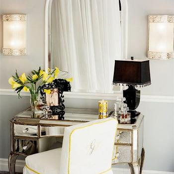Tracy Murdock - bedrooms - antiqued mirrored vanity, mirrored vanity, mirrored make-up vanity, arched mirror, white arched mirror, white slipcovered make-up chair, white slipcovered chair with yellow piping, monogrammed make-up chair, gray carpet, wall to wall carpeting, gray carpeting, gray walls, gray wall color, chair railing, black table lamp, beaded black lampshade, black photo frame, yellow flowers, greek key sconces, contemporary greek key sconces, polished nickel and white glass sconces, polished nickel greek key sconces, Claudia Mirrored Vanity, make up vanity, mirror make up vanity, mirrored make up vanity, Horchow Claudia Mirrored Vanity,