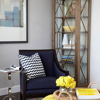 BHG - living rooms - yellow and navy blue living room, yellow and blue living room, light gray walls, glass front curio, curio, curio cabinet, navy blue chair, white and navy chevron pillow, white and navy blue chevron pillow, gray rug, round ottoman, tufted ottoman, yellow ottoman, yellow tufted ottoman, round yellow ottoman, yellow round ottoman, yellow storage ottoman, rope tray, round rope tray, chain link table, chain link accent table,