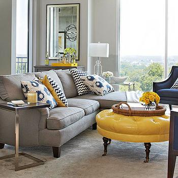 BHG - living rooms - yellow and gray living room, light gray walls, navy blue chair, white and navy chevron pillow, white and navy blue chevron pillow, gray rug, round ottoman, tufted ottoman, yellow ottoman, yellow tufted ottoman, round yellow ottoman, yellow round ottoman, yellow storage ottoman, rope tray, round rope tray, chain link table, chain link accent table, mismatched end tables,