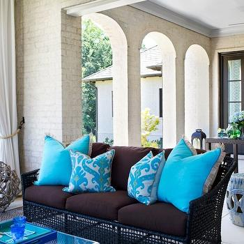 TRI Traci Rhoads Interiors - decks/patios - covered deck, off-white brick, off white brick walls, outdoor drapes, outdoor curtains, outdoor panels, rattan sofa, outdoor furniture, brown wicker sofa, turquoise pillow, turquoise blue pillow, turquoise ikat pillow, turquoise blue ikat pillow,