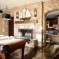 TRI Traci Rhoads Interiors - media rooms - pool room, pool room design, exposed brick wall, arched doorways, brick doorways, iron and glass sconce, accent wall, wallpapered accent wall, rivets wallpaper, phillip jeffries wallpaper, black drum pendants, double drum pendant,