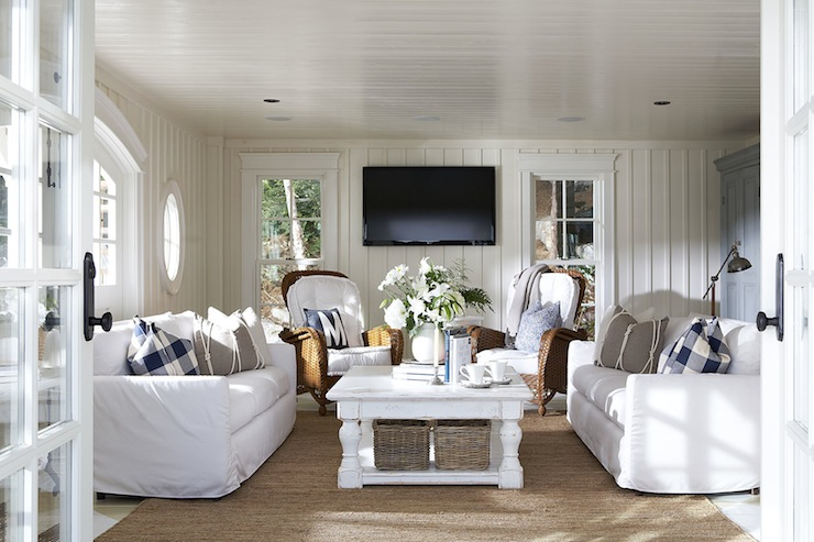 Muskoka Living - living rooms - white sofa, slipcovered sofa, white slipcovered sofa, rattan chair, blue and white plaid pillow, navy and white plaid pillow, linen pillow with rope trim, white coffee table, chunky white coffee table, woven baskets, painted hardwood floors, white painted hardwood floors, rattan chairs, rattan armchairs, navy blue pillow with white letter, blue and white pillow, wood trimmed walls, batten trimmed walls, white walls, monochromatic, monochromatic living room, sisal rug, tv, flat screen tv, wall mounted flat screen tv, sash windows, double hung sash windows, double hung windows, interior french door, matching sofas, matching chairs, cottage living room,