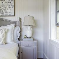 Beautiful monochromatic bedroom with white wood paneled walls and a white ...