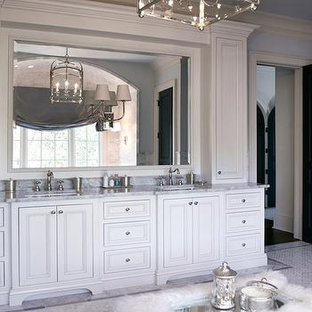 L. Kae Interiors - bathrooms - luxurious bathroom, luxurious master bathroom, bathroom cabinets, white cabinets, white bathroom cabinets, double vanity, white double vanity, custom double vanity, vertical cabinets, cabinet crown molding, crown molding on cabinets, white framed mirror, sconce mounted on mirror, double sconce, his and her sinks, carrara marble countertop, carrara marble subway tile, carrara marble subway tile backsplash, carrara marble backsplash, carrara marble herringbone tile, carrara marble herringbone floor, carrara marble herringbone floor, sheepskin ottoman, sheepskin bathroom ottoman, bathroom ottoman, mercury glass accessories, mercury glass bathroom accessories, mercury glass canisters, medium arch top lantern, visual comfort lighting lanterns, visual comfort lanterns, black door, bathroom, door, black bathroom door, blue walls, blue ceiling, painted ceiling, Visual Comfort Lighting Medium Arch Top Lantern,
