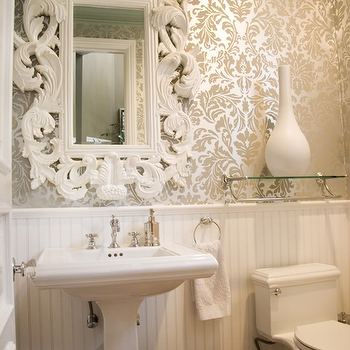Maison Luxe Home - bathrooms - white and gold powder room, white beadboard, beadboard, beadboard wainscoting, beadboard paneled walls, hardwood floors, pedestal sink, traditional pedestal sink, metallic wallpaper, metallic damask wallpaper, gold damask wallpaper, gold in gold damask wallpaper, wallpaper in powder room, wallpapered powder room, ornate white mirror, baroque mirror, white baroque mirror, glass shelf, shelf over toilet, white vase, nickel wastebasket, towel ring, white towels, metallic gold wallpaper, metallic gold damask wallpaper,