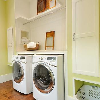 Insidesign - laundry/mud rooms - crown molding, hardwood floors, yellow green walls, green walls, green laundry room walls, green laundry room, white front loading washer, white front loading dryer, folding counter, beadboard backsplash, white beadboard backsplash, recessed cubby, drying rail, chrome drying rail, shelves, built-in cupboards, laundry basket storage, laundry basket cubbies, baseboards, recessed lighting, pot lights, yellow laundry room,
