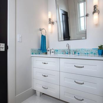 Veranda Interiors - bathrooms - white vanity, white bathroom vanity, built-in vanity, built-in bathroom vanity, single bathroom vanity, polished nickel hardware, polished nickel drawer pulls, white counters, white countertops, blue glass bubble mosaic, blue round mosaic tiled backsplash, turquoise round mosaic tile, turquoise round mosaic tiled backsplash, blue flower pot, blue hand towel, towel ring, pivot vanity mirror, pivot wall mirror, sconces, cylindrical nickel and glass sconces, white hexagonal floor tile, white hex floor tile, hex floor tile, Mosaic Glass Bubble Tile,