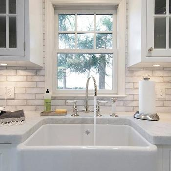 gorgeous sink area with rohl sink gooseneck faucet and white kitchen
