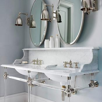 BHG - bathrooms - oval pivot mirrors, pivot mirrors, pimlico sconce, lucite double vanity, lucite double washstand, white carrara marble countertops, carrara marble countertops, carrara marble backsplash, his and her sinks,
