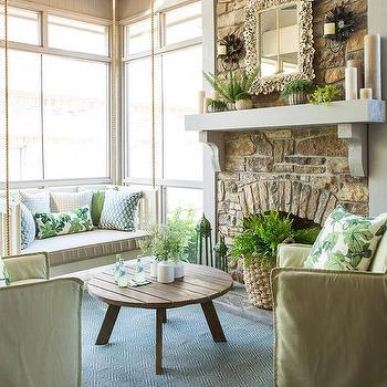 At Home in Arkansas - porches - Rock fireplace, green slipcover chairs, swinging daybed, wooden coffee table, blue geometric rug, blue and green accent pillows,