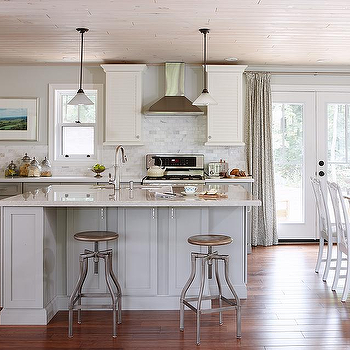 Sarah Richardson Design - kitchens - hardwood floors, wood paneled ceiling, whitewashed wood ceiling, whitewashed wood paneled ceiling, white dining table, white trestle dining table, white dining chairs, patio doors, floor length drapes, gray drapes, gray draperies, gray curtains, kitchen island, gray kitchen island, l-shaped kitchen, white louvered kitchen cabinets, white kitchen cabinets, white kitchen cabinetry, quartz counters, quartz countertops, iron bar stools, iron counter stools, gooseneck faucet, stainless steel appliances, stainless steel fridge, stainless steel refrigerator, stainless steel microwave, stainless steel oven, stainless steel oven hood, gray walls, gray wall color, corner prep sink, louvered kitchen cabinets, louvered kitchen cabinetry, recessed lighting, pot lights, pendants, under counter microwave, Viatera Quartz Denali counter, Terre Verre Silver Lining 2'x4' tile, Viatera Quartz Natural Limestone counter, light gray island, light gray kitchen island,