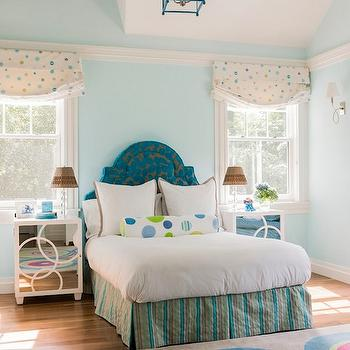 Jill Litner Kaplan Interiors - girl's rooms - blue walls, blue wall color, vaulted ceiling, peacock blue lantern pendant, lantern pendant, hardwood floors, mirror fronted nightstand, white lacquered mirror fronted nightstand, peacock blue arched headboard, arched headboard, arched upholstered headboard, striped bed skirt, box pleated bed skirt, white bedding, white bed linens, green and blue polka dot bolster pillow, bolster pillow, roman shades, green and blue polka dot roman shades, crystal stacked sphere table lamps, multi-colored rug, multi-colored geometric rug, hardwood floors, sash windows, Leah Nightstand in Marshmallow Lacquer, peacock blue headboard, peacock blue lantern,