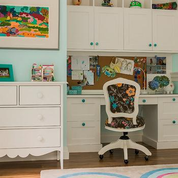 Jill Litner Kaplan Interiors - dens/libraries/offices - homework station, built-in desk, built-in cabinets, built-in kids desk, built-in kids workstation, white built-in desk, turquoise hardware, desk chair on castors, girls desk chair, floral desk chair, hardwood floors, white dresser, multi-colored art, pinboard backsplash, cork board backsplash, blue walls, blue wall color, girls desk, girls built in desk,