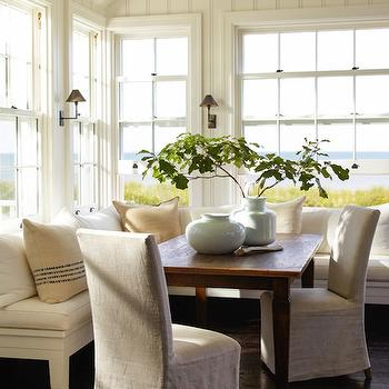 Sawyer Berson - dining rooms - tongue and groove walls, L shaped banquette, L shaped dining banquette, white dining banquette, L shaped sining banquette, farmhouse dining table, blue vases, slipcovered dining table, linen dining chairs, vintage grain sack pillows,