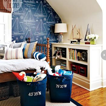 Style at Home - boy's rooms - nautical bedroom, nautical boys room, nautical kids room, navy and white sailing wallpaper, sailing wallpaper, boat wallpaper, yacht wallpaper, nautical wallpaper, hardwood floors, jenny lind bed, seagrass baskets, navy canvas tote, tote with embroidered bearings, light jute rug, blue beige and white striped pillow, navy and white pillow, beige and white striped pillow, woven blinds, woven blinds with white trim, navy and white striped bolster pillow, model boats, model yachts, books, kids bookshelves, toys, canvas totes, glass bottle lamp, white bookshelves, bookshelves, built-in kids bookshelves, nautical wallpaper, boys wallpaper, blue nautical wallpaper, navy nautical wallpaper, sailing themed wallpaper,