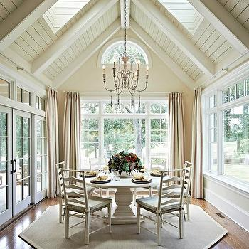 Carolina Design Associates - dining rooms: sunroom, sun room, wall to wall windows, floor length drapes, floor length draperies, red green and cream striped drapes, vaulted ceilings, skylights, sky lights, wood paneled ceiling, wood paneling, cafe au lait walls, cafe au lait wall color, crescent shaped window, painted wood paneled ceiling, hardwood floors, ivory round pedestal dining table, round pedestal dining table, hexagonal shaped rug, hexagonal shaped jute rug, ivory ladder back chairs, ladder back dining chairs, tie on seat cushions, carved wood and iron chandelier, french style chandelier, patio doors, french doors, dine in sunroom, ladder back chairs, ladder back dining chairs, dining room skylights,