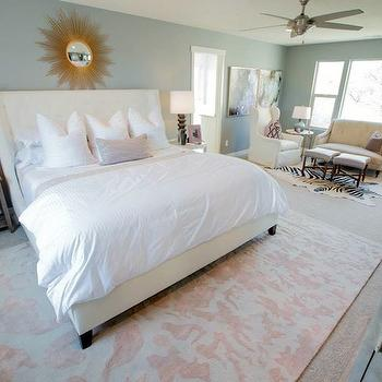 Henry Walker Homes - bedrooms - blue walls, blue wall color, wall to wall carpet, carpet, beige carpet, rug on carpet, rug over carpet, pink and white rug, pink and white patterned rug, zebra print hide rug, zebra print rug, slipcovered wingback chair, linen colored settee, upholstered stools, round side table, blue table lamp, abstract art, abstract artwork, round white nightstand, mismatched nightstand, brown stacked sphere lamps, white bedding, white bed linens, white sheets, lavender pillow, sunburst mirror, gold sunburst mirror, recessed lighting, pot lights, ceiling fan, brushed nickel ceiling fan, ivory headboard, upholstered ivory colored bed, ivory tufted headboard, stacked sphere table lamp, gold greek key floor lamp, Le Chic Gold Floor Lamp, gold starburst mirror, gold starburst mirror,