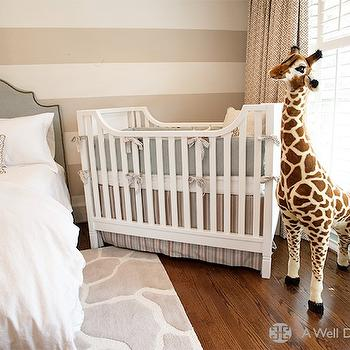 A Well Dressed Home - nurseries - nursery guest room, guest room nursery, striped walls, striped nursery walls, striped boys nursery, white and tan striped walls, white moose head, studded headboard, gray headboard, studded gray headboard, gray linen headboard, gray headboard with nailhead trim, boys nursery, nursery giraffe, giraffe rug, gray giraffe rug, white and gray giraffe rug, white crib, tan geometric curtains, Melissa & Doug Plush Giraffe,