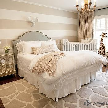 A Well Dressed Home - nurseries - nursery guest room, guest room nursery, striped walls, striped nursery walls, striped boys nursery, white and tan striped walls, white moose head, studded headboard, gray headboard, studded gray headboard, gray linen headboard, gray headboard with nailhead trim, mirrored nightstand, boys nursery, nursery giraffe, giraffe rug, gray giraffe rug, white and gray giraffe rug, white crib, Melissa & Doug Plush Giraffe,