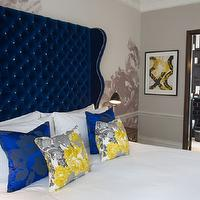 The Ampersand Hotel - bedrooms - tall headboard, indigo blue headboard, indigo blue velvet headboard, indigo blue tufted headboard, indigo blue wingback headboard, indigo blue pillows, yellow and gray pillows, light gray walls, chair rail, bedroom chair rail, chair rail in bedroom,