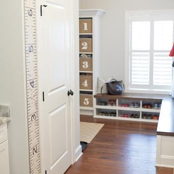 Britt Lakin Photography - laundry/mud rooms - light gray walls, light gray paint, light gray paint colors, wickham gray, L shaped bench, mud room, mud room ideas, mudroom ideas, mudroom bench, built in bench, bench with cubbies, bench with shoe cubbies, shoe cubbies, white bookcase, wicker baskets, numbered baskets, wicker numbered baskets, schoolhouse pendant, hanging ruler, Etsy Hanging Ruler,