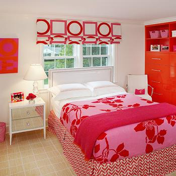 Robyn Karp Interiors - girl's rooms - red and pink girls room, white leather headboard, upholstered white leather headboard, white leather headboard with nailhead trim, grid patterned carpet, patterned carpet, mirror fronted nightstand, white nightstand with mirror front, mirror front nightstand, glass table lamp, glossy red built-ins, built-in drawers, white leather desk chair, white leather and chrome desk chair, pleated bed skirt, red and white pleated bed skirt, chevron arrow bed skirt, pink and red floral bedding, pink throw, pink and red floral coverlet, red and white geometric roman shades, red and white geometric drapes, red and white geometric curtains, polished nickel hardware, red and pink girls room, red and pink girls bedroom, Victoria Hagan Summer Squares Fabric,