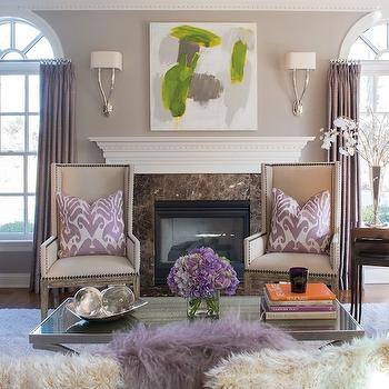 Susan Glick Interiors - living rooms - purple curtains, purple drapes, purple window panels, arched windows, ruhlmann sconce, abstract art, fireplace art, dentil molding, fireplace mantle, fireplace millwork, fireplace surround, brown marble fireplace surround, linen wingback chairs, wingback chairs, purple ikat pillows, nesting tables, black nesting tables, mirrored top coffee table, purple velvet chairs, purple french chairs,