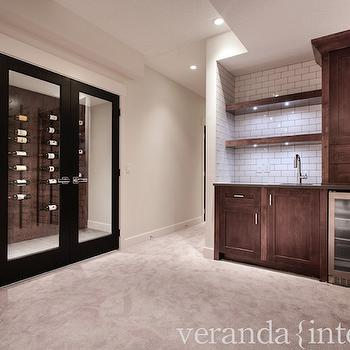Veranda Interiors - basements: cafe au lait walls, cafe au lait wall color, beige carpet, beige carpeting, wall to wall carpet, wet bar, basement wet bar, stainless steel glass front beverage fridge, glass front beverage fridge, glass front wine fridge, coffee stained cabinets, floating shelves, stained wood floating shelves, black glass door, black glass paned door, wood paneled walls, wood paneling, wine room, wine cellar, wine storage, wall mounted wine storage, wine bottle storage, rustic wine storage, wine cellar storage, wine cellar display, vertical wine bottle storage, iron wine bottle storage, vertical iron wine bottle storage, subway tile, subway tiled backsplash, subway tile with gray grout, subway tile with dark grout, polished nickel hardware, gooseneck faucet, basement wine room, basement wine cellar, wine cellar,