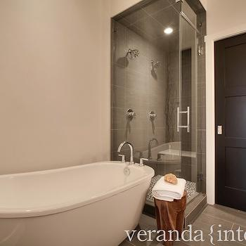 Veranda Interiors - bathrooms - Benjamin Moore - Black - freestanding bath, freestanding tub, soaking tub, gooseneck faucet, gray tiled floor, gray floor tile, gray bathroom floor tile, gray shower surround, gray tiled shower surround, walk-in shower, glass shower enclosure, seamless glass shower door, black door, black interior door, black bathroom door, monochromatic, monochromatic bathroom, shower lighting, shower lights, gray shower tiles,