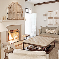 Rachel Halvorson Design - living rooms - living room wood beams, white fireplace mantle, reclaimed wood doors, hidden TV, concealed TV, fireplace TV, TV over fireplace, herringbone firebox, monochromatic living room, gray sofa, ottoman coffee table, cream leather tufted ottoman, cream leather ottoman, square ottoman, cream tufted ottoman, ivory sofa, ivory chairs, slipcovered armchairs, ivory slipcovered armchairs, brass floor lamp, french doors, living room french doors, gray french doors, french doors and transom windows, botanical art gallery,