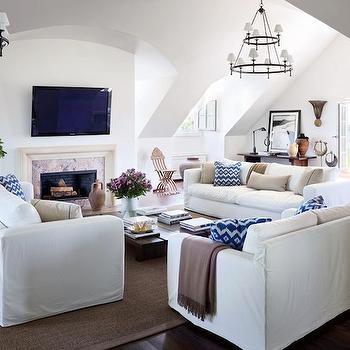 Architectural Digest - living rooms - white walls, white wall color, white slipcovered sofa, slipcovered sofa, sofa table, dark hardwood floors, hardwood floors, jute rug, bound jute rug, olive jars, glass vessel, blue and white pillow, neutral pillow, coffee table, low wooden coffee table, vaulted ceilings, stone fireplace surround, carved stone fireplace surround, tv over fireplace, flat screen tv over fireplace, french doors, wooden console, plantation chair, floor lamp, fireplace, black and white framed art, corbels, stacked books, indigo blue and white pillows, iron chandelier, round iron chandelier, tiered iron chandelier, slipcover sofas, white slipcover sofas,