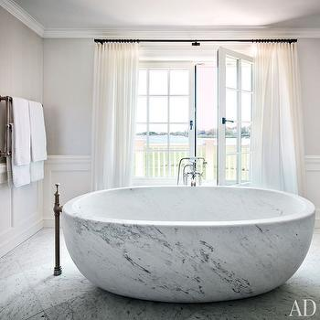 Architectural Digest - bathrooms - marble tub, marble bath, freestanding marble tub, freestanding marble bath, marble tiled floors, marble floor tile, floor tile laid on diagonal, floor mounted faucet, french doors, bathroom french doors, balcony, floor length drapes, floor length curtains, white drapes, white curtains, wainscoting, gray walls, gray wall color, towel rail, waterworks fittings, monochromatic, monochromatic bathroom, marble freestanding tub, bathroom wainscoting, master bathroom wainscoting,