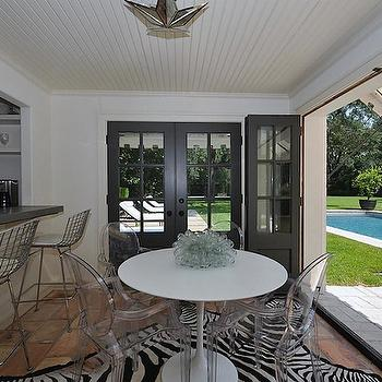 HAR - decks/patios - pool house, pool house ideas, pool house design, beadboard ceiling, star pendant, mirrored star pendant, saarinen table, ghost chairs, zebra rug, zebra cowhide rug, terracotta floor, black doors, folding doors, black folding doors,