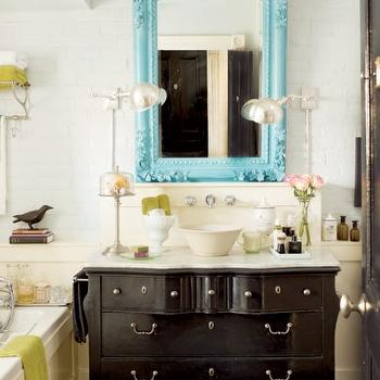 decormag - bathrooms - turquoise accents, turquoise blue accents, baroque mirror, turquoise baroque mirror, turquoise blue baroque mirror, blue baroque mirror, turquoise french mirror, black washstand, chest washstand, black bathroom vanity, black vanity with white marble top, cream wainscoting, cream paneled bathtub, cream paneled tub, bathroom wainscoting, white brick wall, train rack, bathroom train rack, train rack over bathtub, train rack over tub, train rack above bathtub, train rack above tub, staggered tile, gray staggered tile, gray floor tiles, slate tiles, slate tile floor, bowl sink, wall mounted faucet,