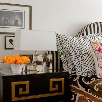 Jill Litner Kaplan Interiors - bedrooms - white walls, white wall color, black nightstand, black nightstand with greek key trim, black nightstand with gold greek key overlay, black bedside table with gold greek key trim, gold clock, white vase, orange roses, brown and white rectangular lamp, suzani bedding, suzani quilt, suzani coverlet, black and white geometric pillows, black and white geometric shams, framed silhouette, framed black and white print, black and white headboard, black and white striped headboard, black and white upholstered striped headboard, black and gold greek key nightstand, greek key nightstand, greek key chest,