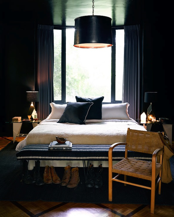 Harper's Bazaar - bedrooms - black bedroom, black walls, black ceiling, black bedroom walls, charcoal gray drapes, charcoal gray curtains, floor length drapes, floor length curtains, bed in front of window, matching nightstands, white bedding, white bed linens, white bed sheets, black pillows with white piping, wool blanket, black and white bench, black and white bench with hairpin legs, bench at end of bed, bench at foot of bed, parquet floors, diamond patterned parquet floors, black rug, woven chair, black drum pendant, black metal drum pendant, modern white glass topped nightstands, gold table lamp, gold table lamp with black shade, faceted gold table lamp, bed in front of window, white and black bedroom, black ceiling,