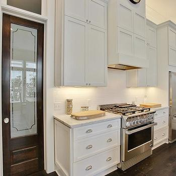 Troyer Builders - kitchens - creamy white cabinets, carrera marble, carrera marble countertops, paneled range hood, paneled hood, cabinets above fridge, pantry door, frosted glass pantry door, glass pantry door, pantry door ideas, rustic wood floors, wide plank floor, wide plank wood floor,
