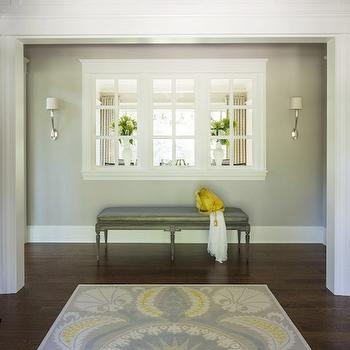 Martha O'Hara Interiors - entrances/foyers: interior window, window through to living room, hardwood floors, dark hardwood floors, blue yellow white and gray rug, blue yellow and gray suzani rug, suzani style rug, nickel sconce, nickel sconce with ivory shade, glass bubble chandelier, glass bubble pendant, gray bench, gray walls, gray wall color, sconces flanking window, yellow and gray foyer, yellow and gray rug, gray bench, gray silk bench,